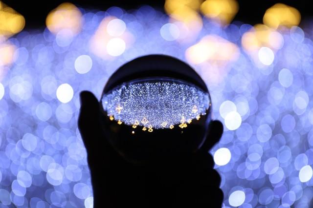 手に持つガラス玉に写り込むイルミネーション(神戸ルミナリエ)の写真