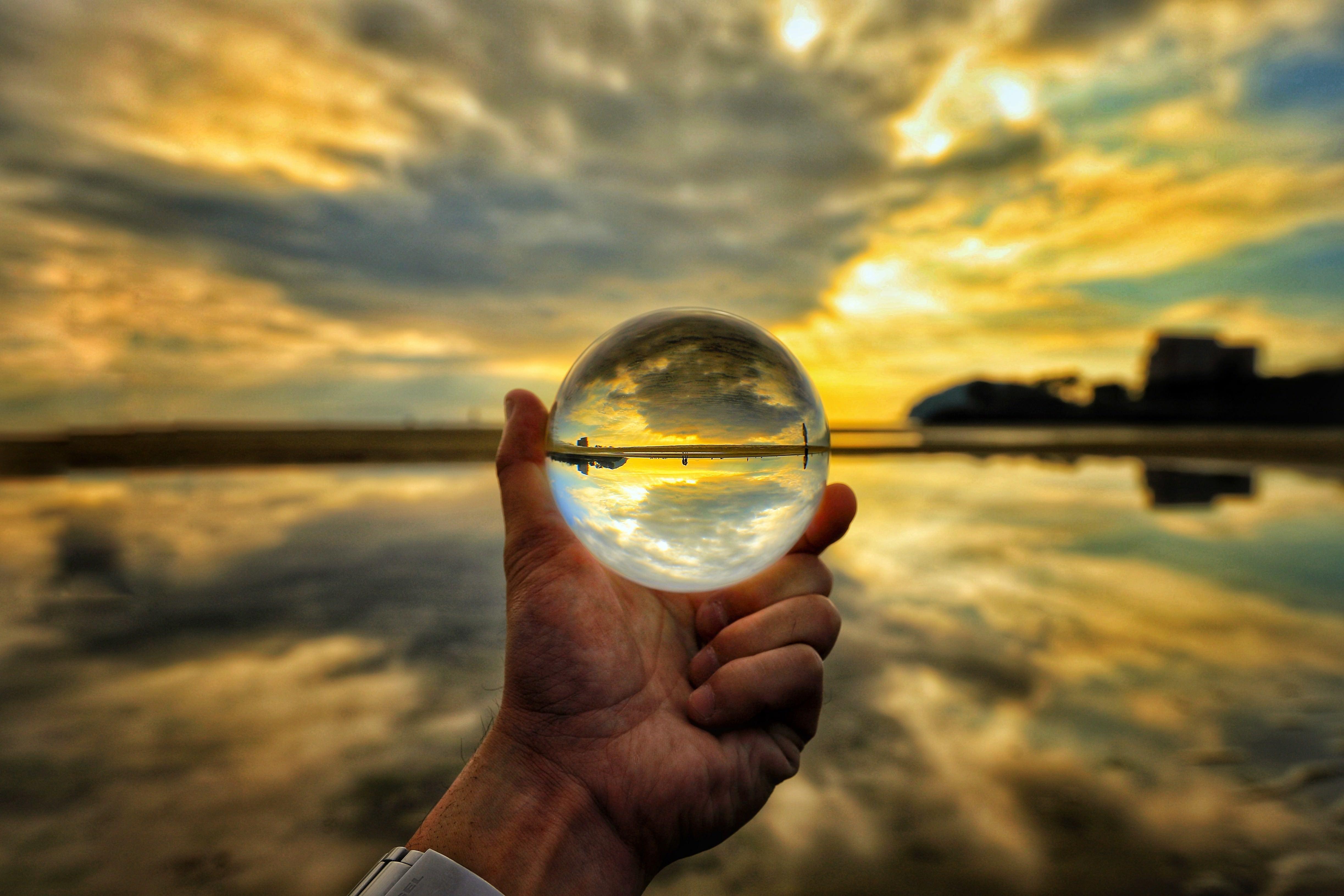 ガラス玉の中の夕焼けと浜辺の写真