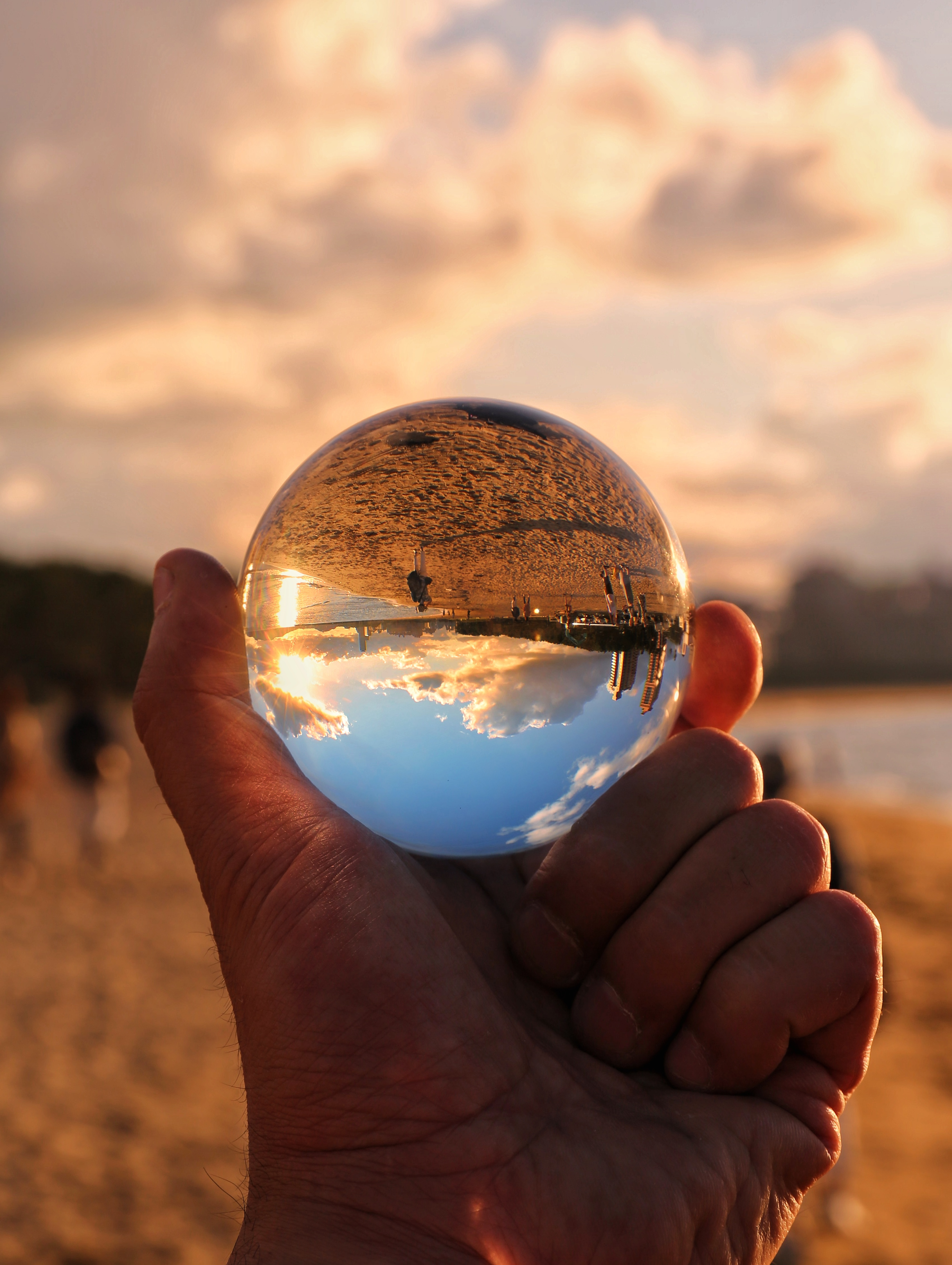 水晶球越しに見る夏の浜辺の写真