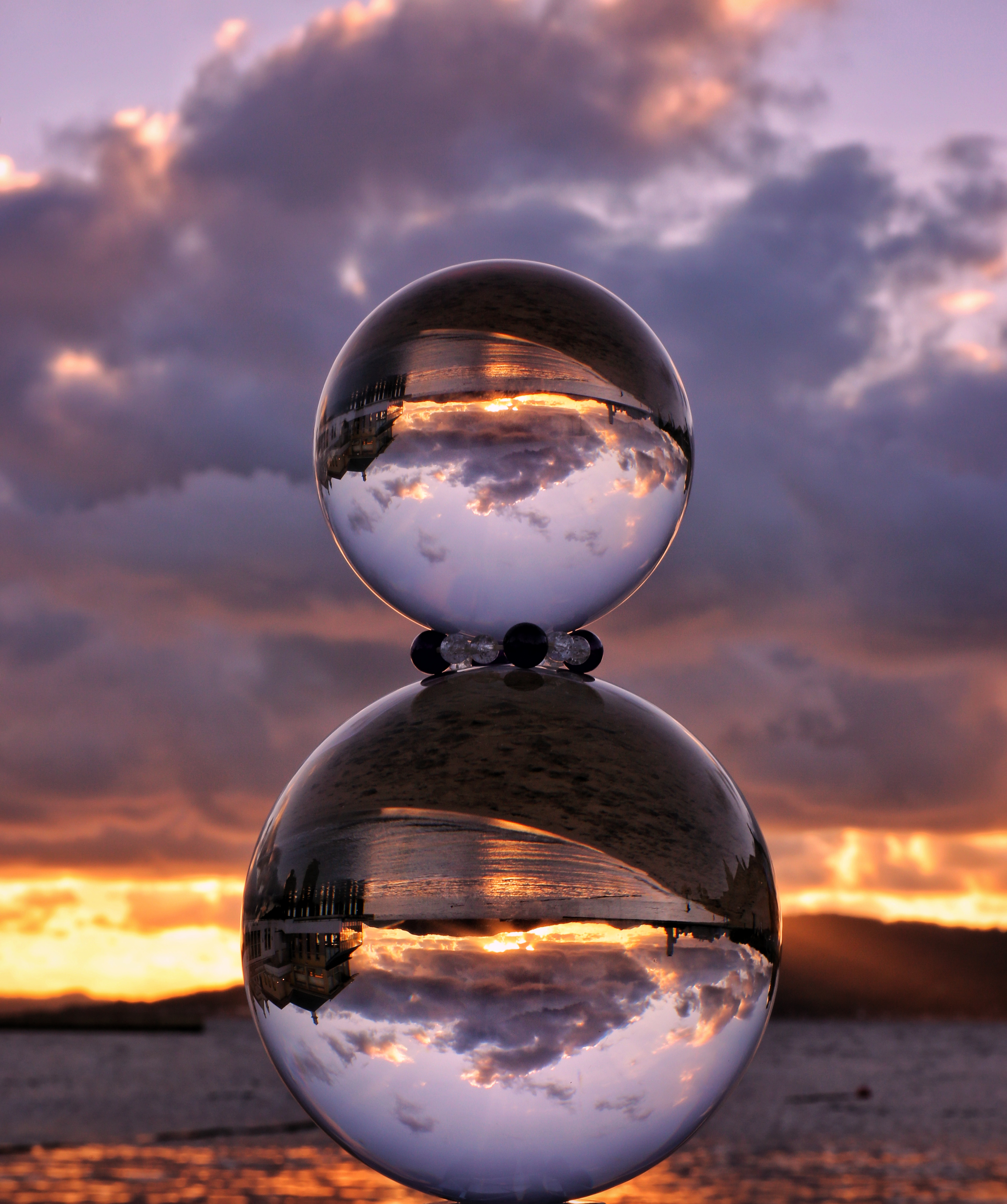 重ねた水晶球と夕暮れの海岸の写真