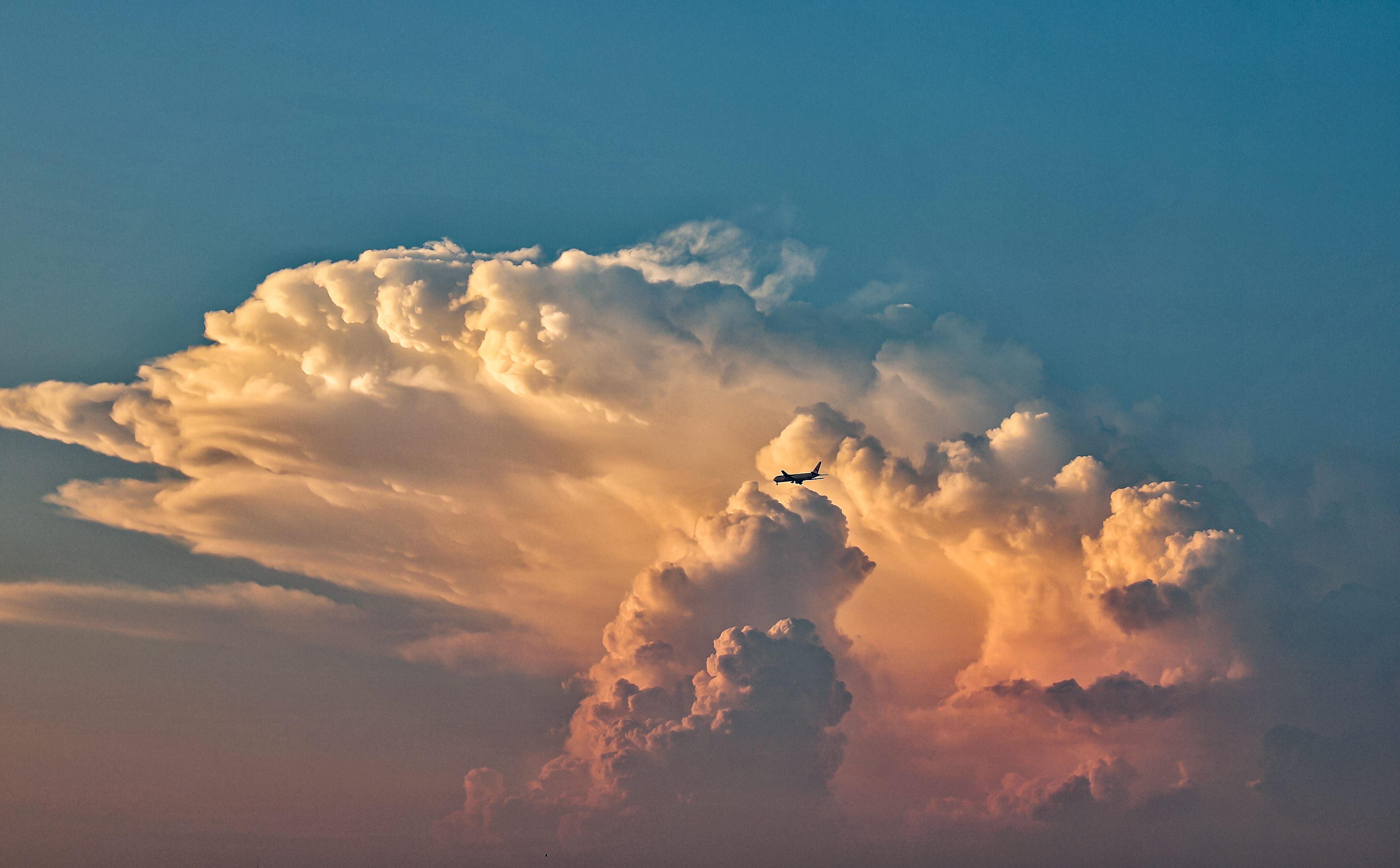 「夕焼けに染まる入道雲と飛行機」の写真