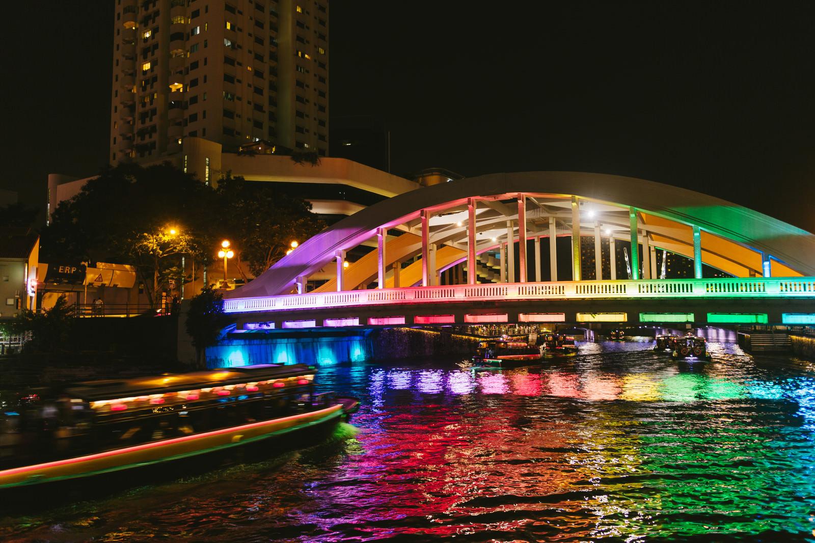 「虹色にライトアップされた橋と屋形船(シンガポール)」の写真