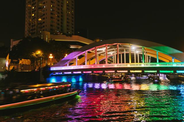 虹色にライトアップされた橋と屋形船(シンガポール)の写真