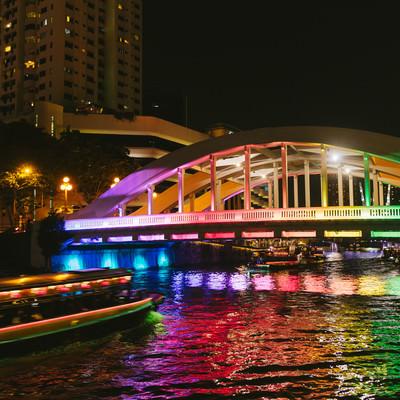 「虹色にライトアップされた橋と屋形船(シンガポール)」の写真素材