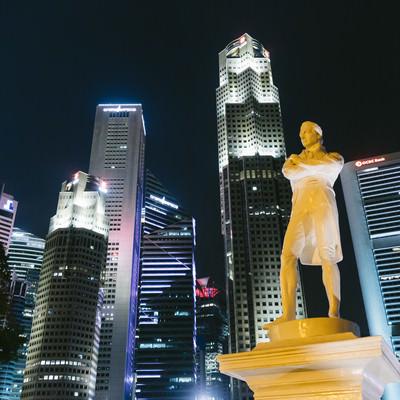 ラッフルズ像とビル群(夜景)の写真