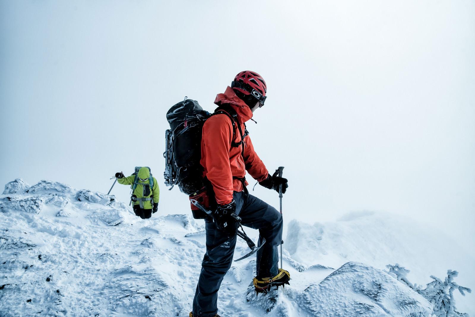 「雪山で下山路を見つめる登山者の男性」の写真