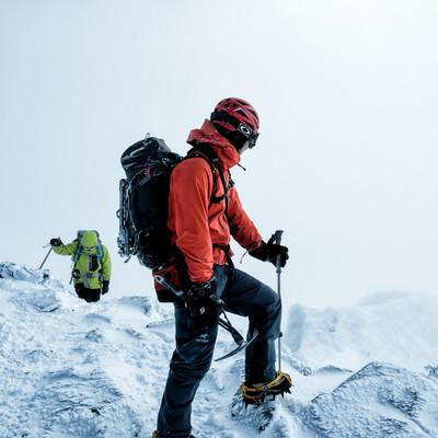 雪山で下山路を見つめる登山者の男性の写真