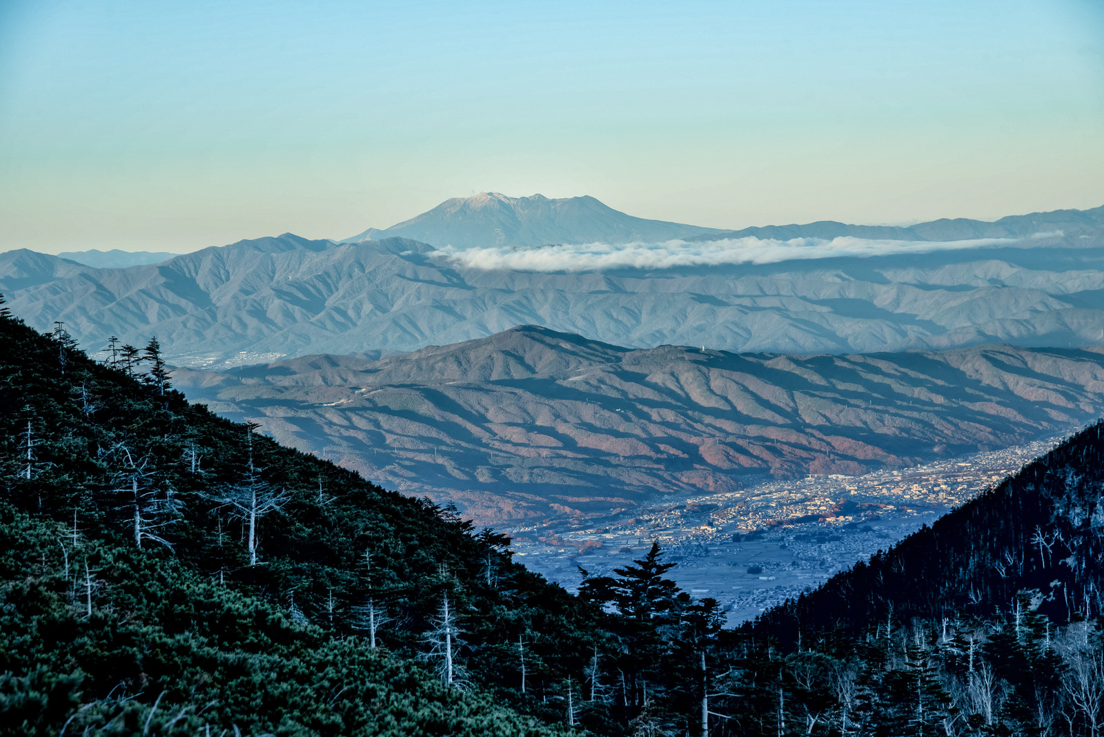 「晩秋の山々と霞む空の御嶽山」の写真