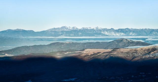 霞む空と遠くに見える北アルプスの写真