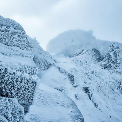 立ち込めるガスで視界不良の雪山の写真