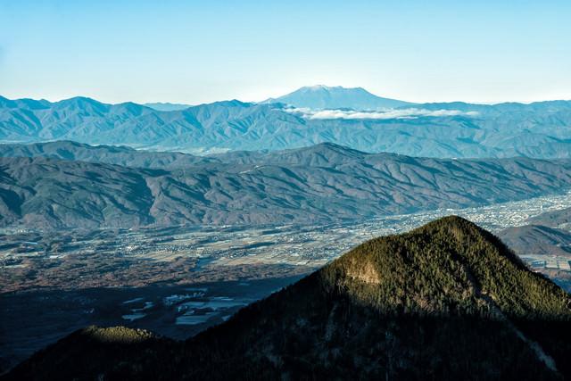麓の町並みと遥か遠くの御嶽山の写真