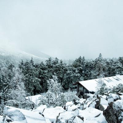 視界不良の雪山と雪に覆われた高見石小屋の写真