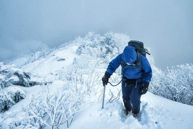 雪深い登山道で山頂を目指す登山者の写真