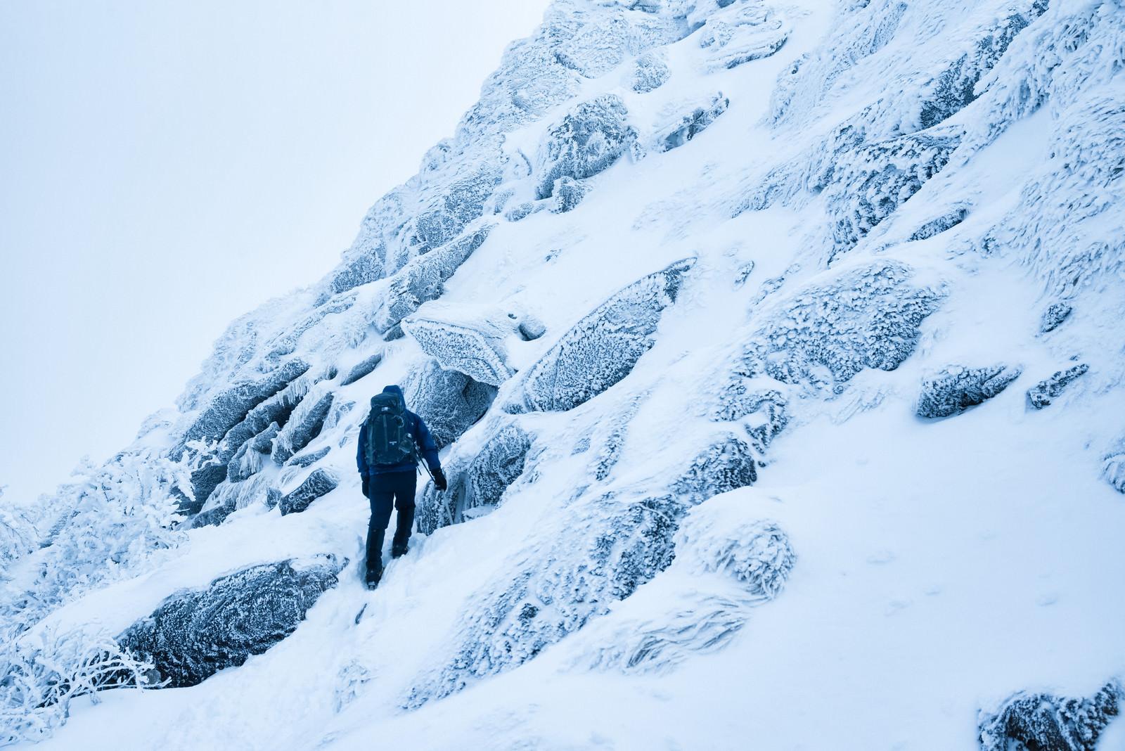 「雪の斜面をトラバースする登山者」の写真