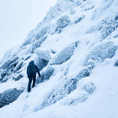 雪の斜面をトラバースする登山者の写真