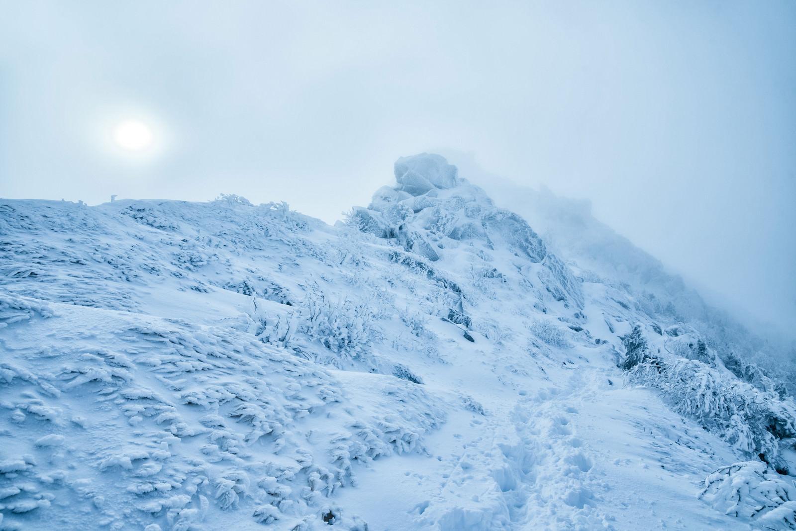 「立ち込めるガスに隠れた太陽と積雪の稜線」の写真