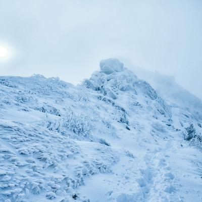 立ち込めるガスに隠れた太陽と積雪の稜線の写真