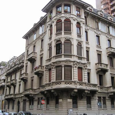 ミラノの通りの角に面した歴史を感じる建物(イタリア)の写真