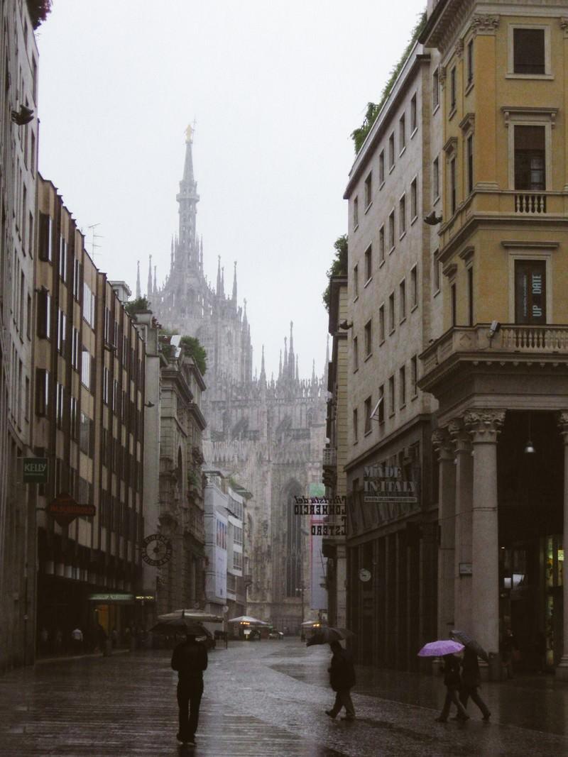 「ミラノの大聖堂へと続く路地で傘を差す通行人(イタリア)」の写真