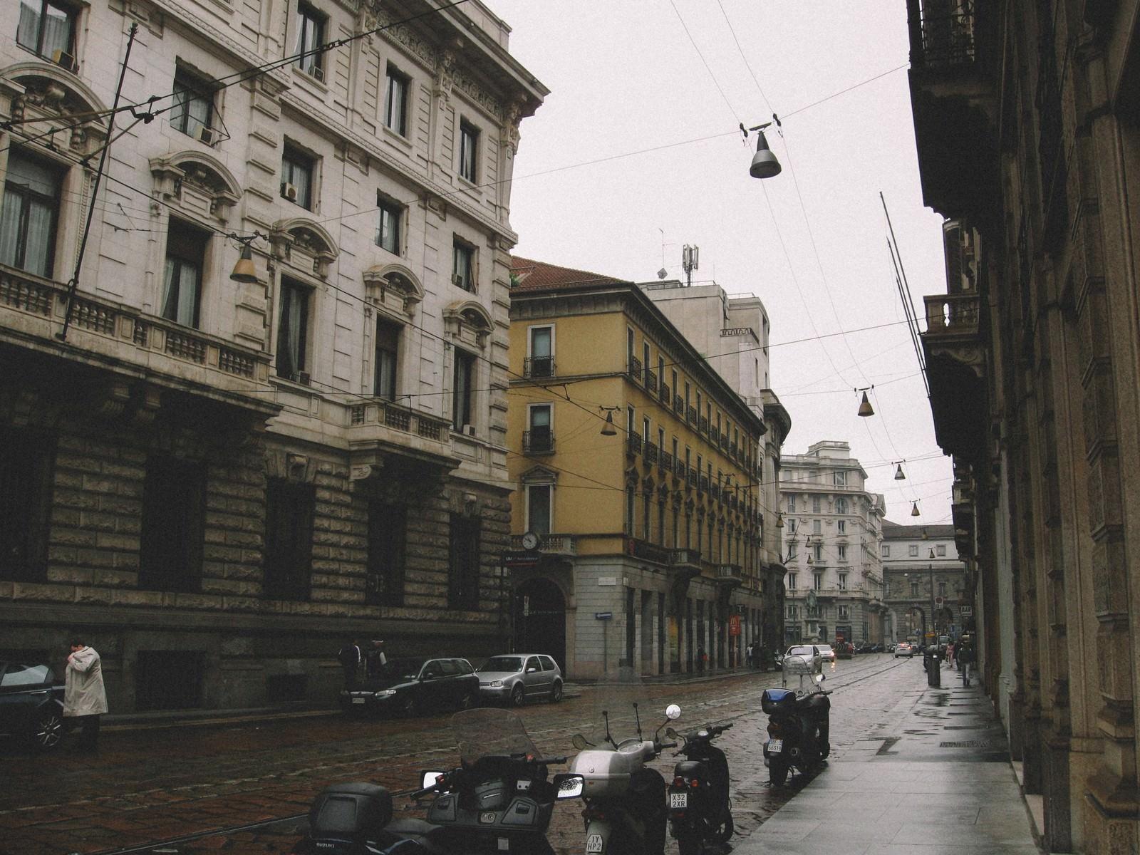 「雨上がりの濡れた路地に停められたバイク(イタリア ミラノ)」の写真