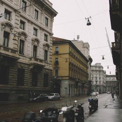 雨上がりの濡れた路地に停められたバイク(イタリア ミラノ)の写真