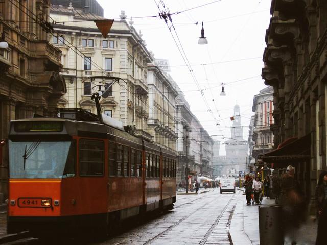 ミラノの時計台へと続く路地を走る路面電車と街並み(イタリア)の写真