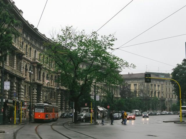 ミラノの街並みと車道と平行して走る路面電車(イタリア)の写真