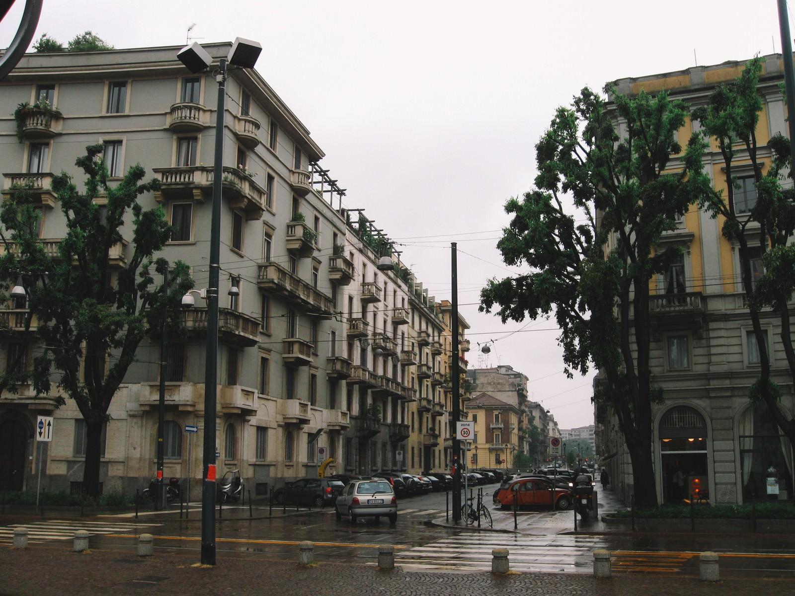 「街角のパーキングに駐車している車と街並み(イタリア ミラノ)」の写真
