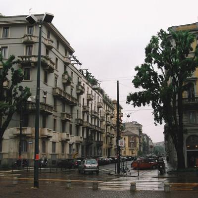 街角のパーキングに駐車している車と街並み(イタリア ミラノ)の写真