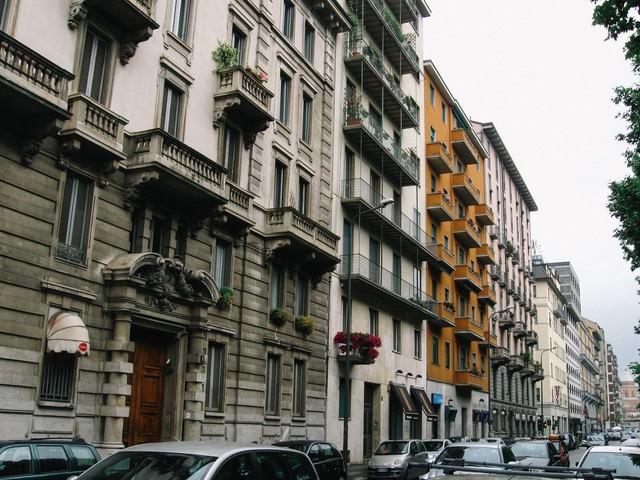 ミラノの通りを行き交う車と通りに面した建造物(イタリア)の写真