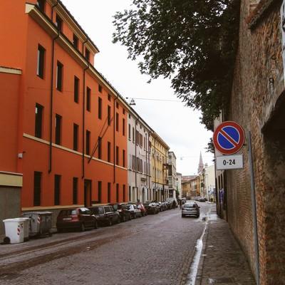 マントヴァの街角に駐車する車とレンガ造りの壁前に立つ標識(イタリア)の写真
