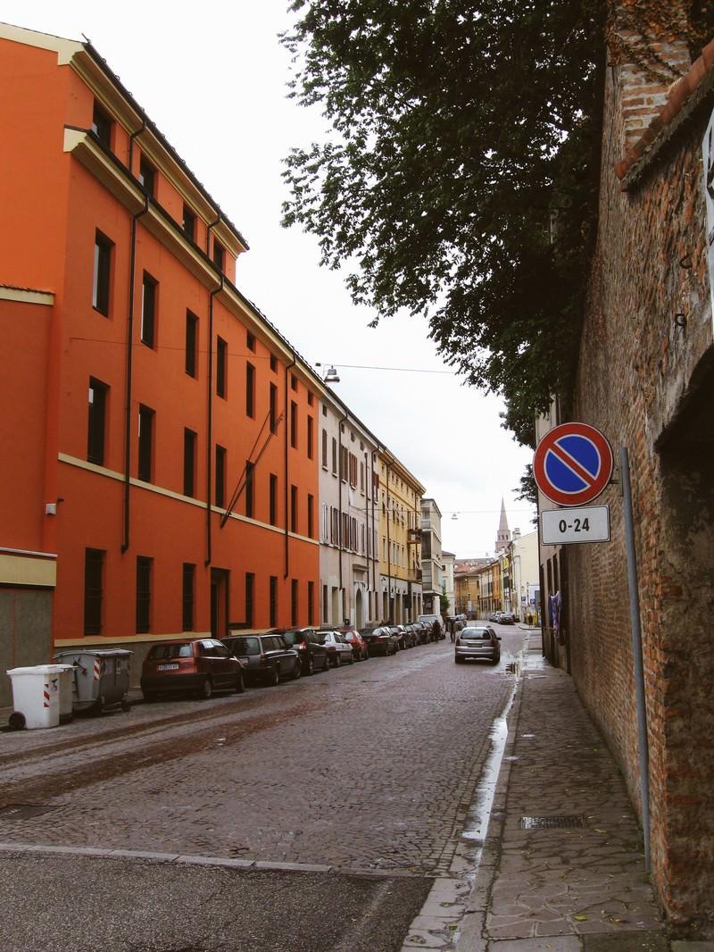 「マントヴァの街角に駐車する車とレンガ造りの壁前に立つ標識(イタリア)」の写真