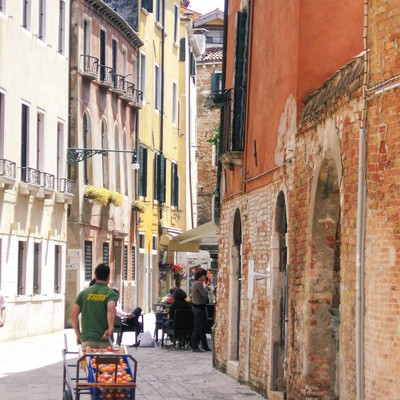 ベネチアの街並みと果物売りの青年(イタリア)の写真