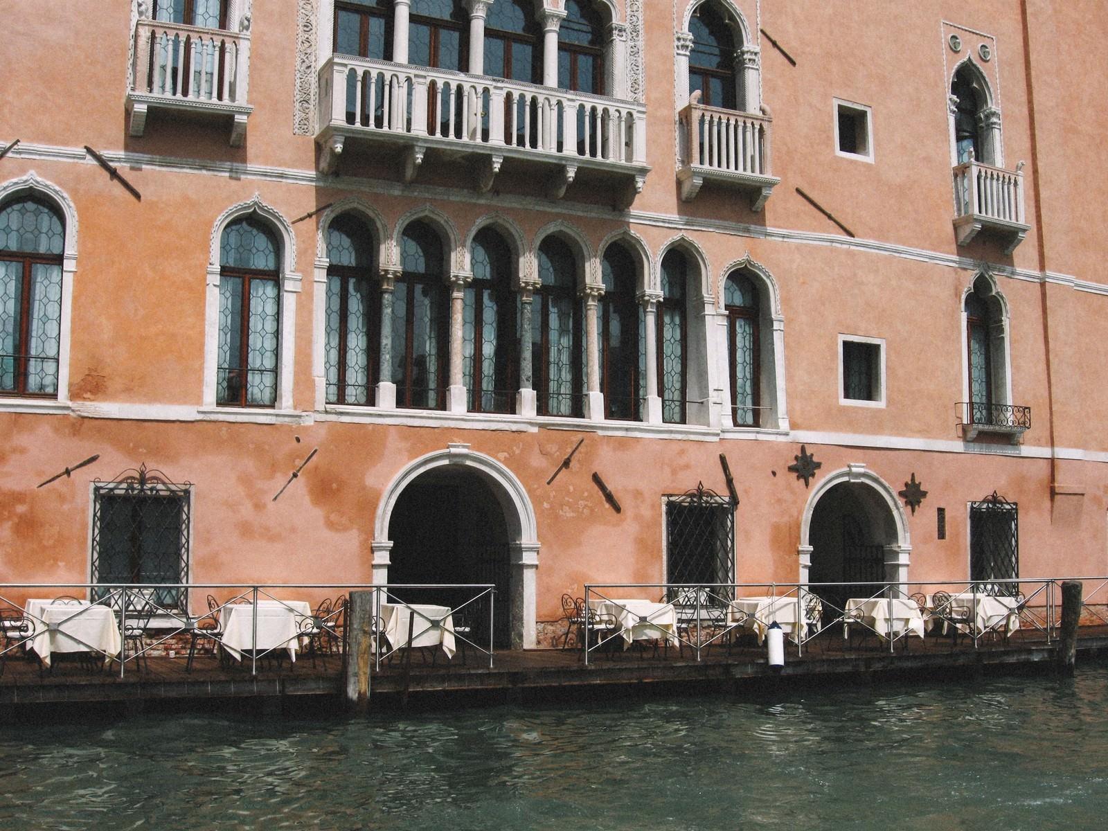 「ヴェネツィアの川沿いにあるレストランの白いテーブル(イタリア)」の写真