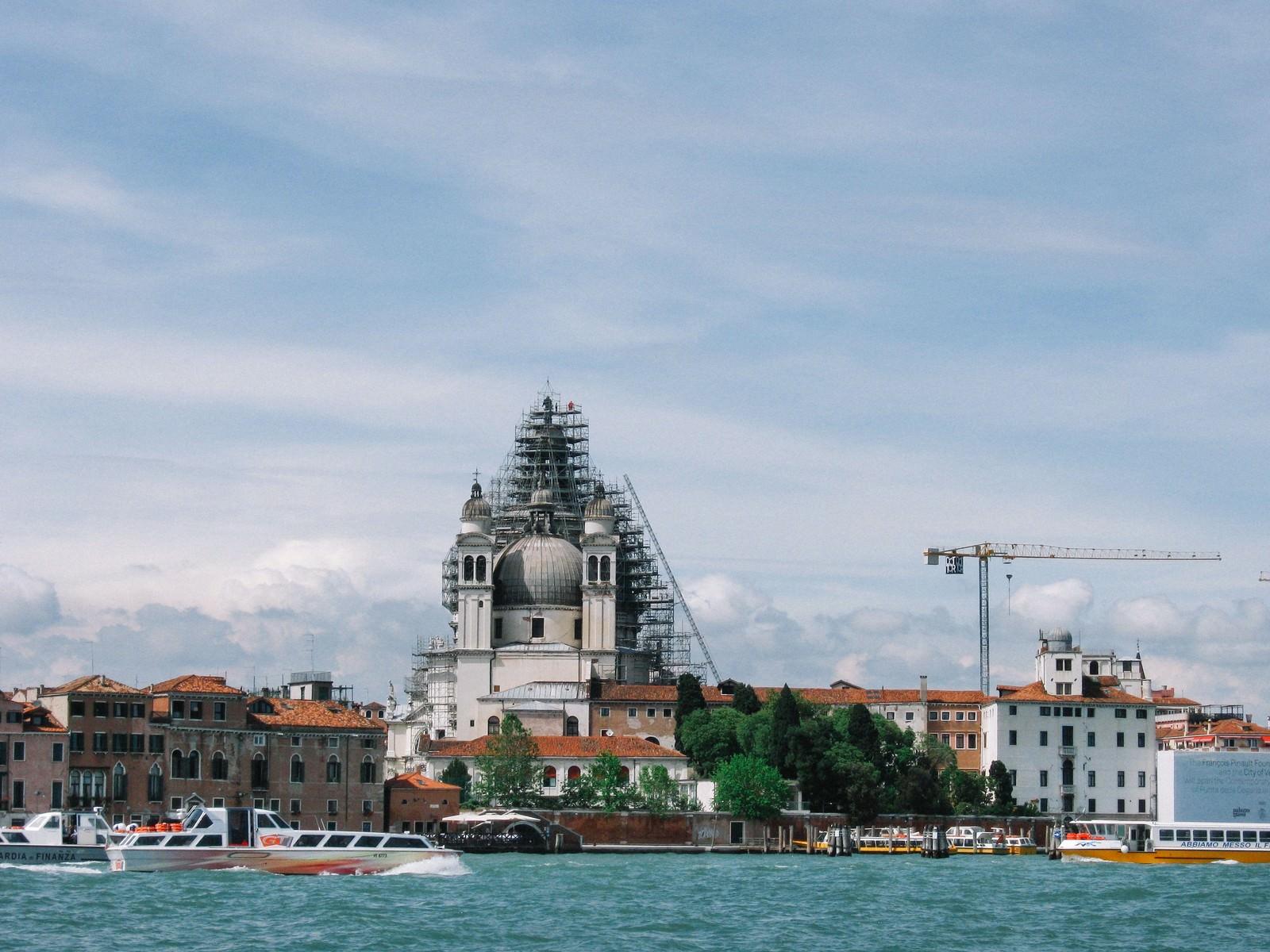 「ヴェネツィアを流れる川と街並みの向こうに見えるサンタ マルサ デッサ サルーテ教会(イタリア)」の写真