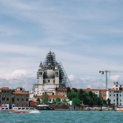 ヴェネツィアを流れる川と街並みの向こうに見えるサンタ マルサ デッサ サルーテ教会(イタリア)の写真