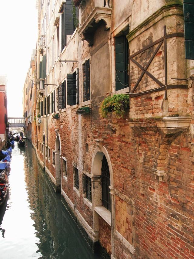 ヴェネツィアの水路に浮かぶゴンドラとレンガ造りの建物(イタリア)の写真