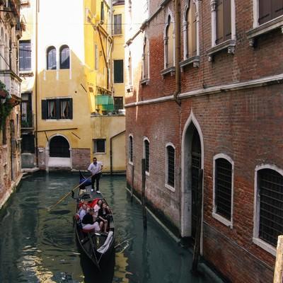ヴェネツィアの水路をゴンドラで進む観光客(イタリア)の写真