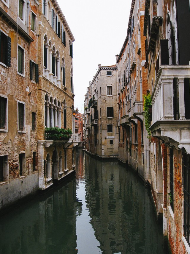 レンガ造りの建物沿いを流れるヴェネツィアの水路(イタリア)の写真