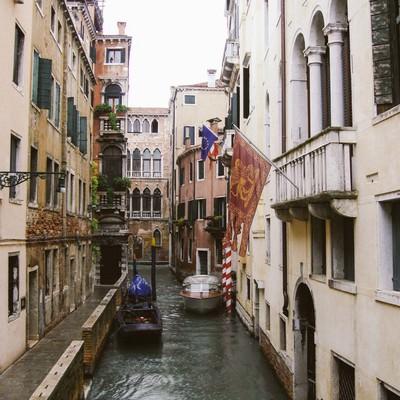 ヴェネツィアの水路に浮かぶ小船と旗が立つ建物(イタリア)の写真