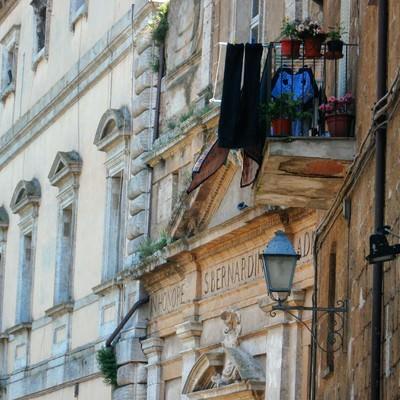 オルヴィエートの出窓に並ぶ花と洗濯物(イタリア)の写真