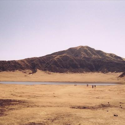 麓の湖畔に集まる観光客の写真