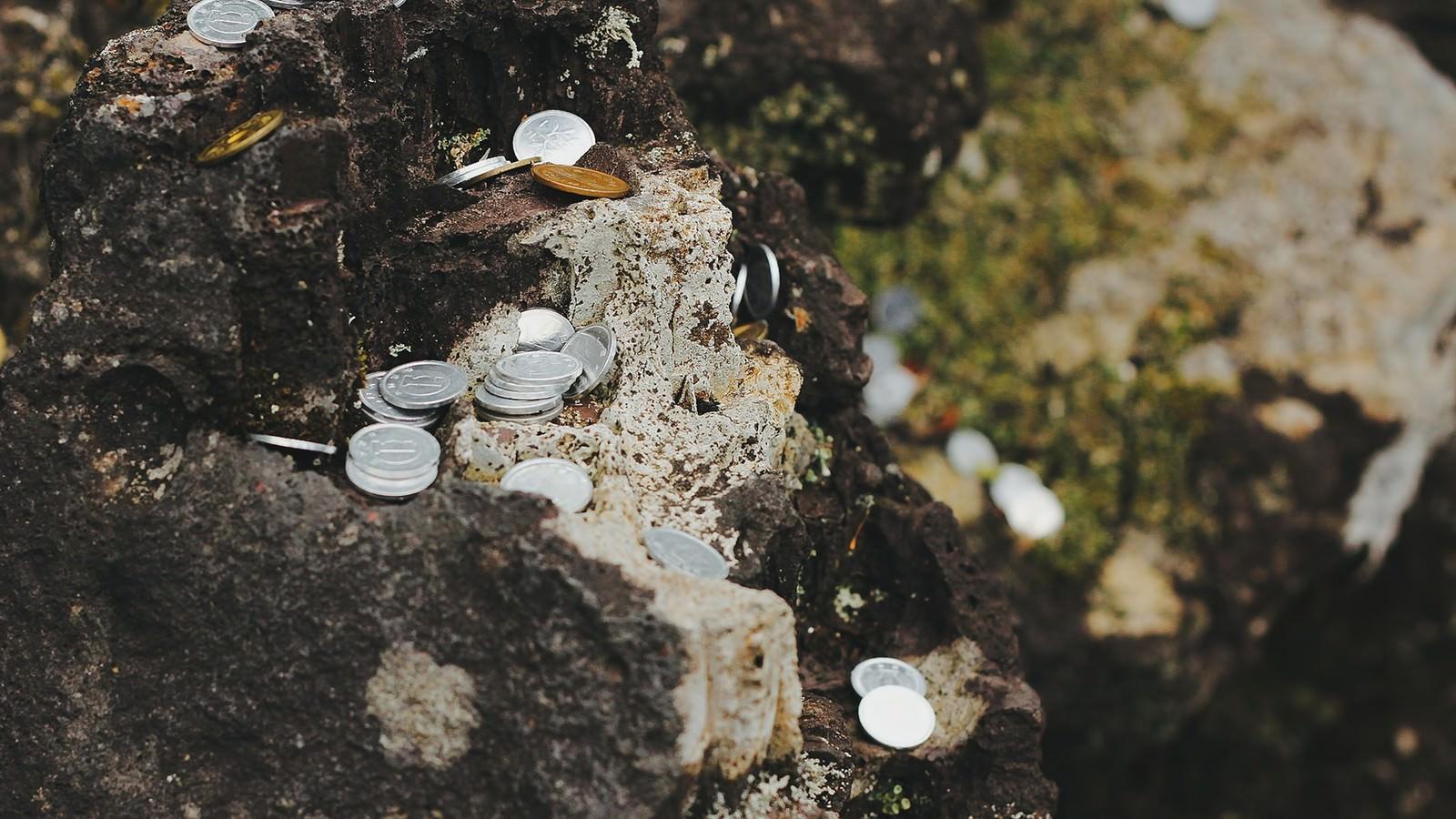 「岩場に置かれた小銭」の写真