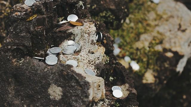 岩場に置かれた小銭の写真