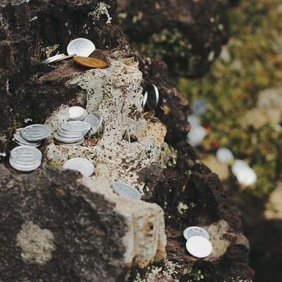 「岩場に置かれた小銭」の写真素材