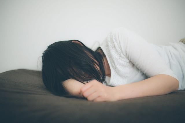 ひとり腕枕で寂しさを紛らわす失恋女子の写真