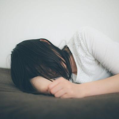 「ひとり腕枕で寂しさを紛らわす失恋女子」の写真素材