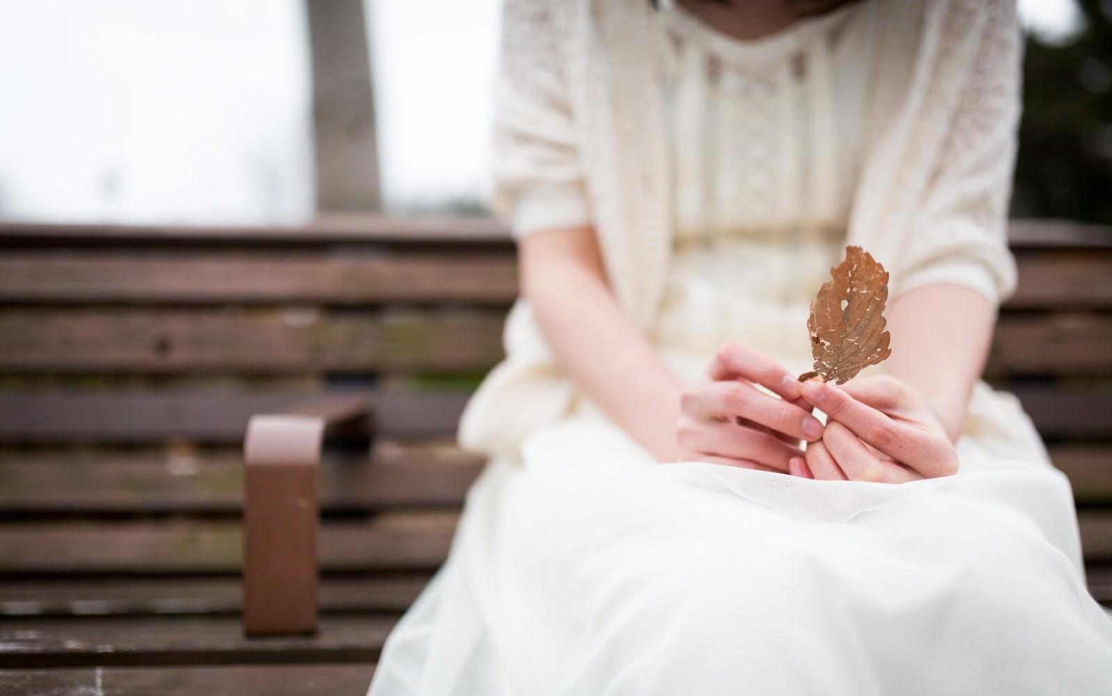 「心情と枯れ葉を重ねる女性」の写真[モデル:たけべともこ]