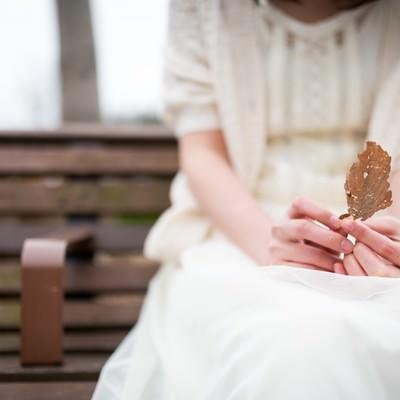 「心情と枯れ葉を重ねる女性」の写真素材