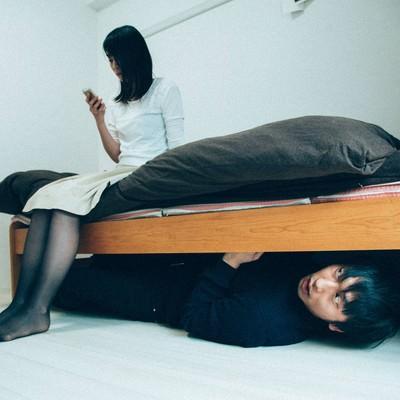 「ベッドの下の男」の写真素材